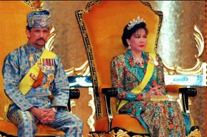 The Sultan of Brunei, Hassanal Bolkiah, and his second wife, Hajah Mariam, look slightly solemn during the sultan's 50th birthday celebrations in Bandar Seri Begawan.