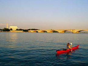 In Washington's Potomac River,a woman kayaks past the Lincoln Memorial toward Memorial Bridge.
