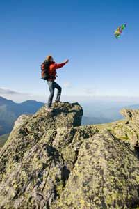 A hiker flying a kite in high winds atop Mount Washington
