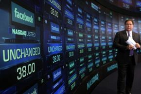 A reporter waits for trading to begin on Facebook stock, minutes before its initial public offering on May 18, 2012.
