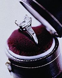 Channel-set diamonds flank this gorgeous emerald-cut stone.
