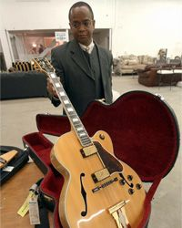 Mark Green with the IRS holds a guitar owned by singer Peabo Bryson in 2003. Much of Bryson's things were being auctioned off to pay a tax debt.