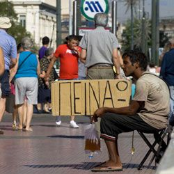 """A Greek beggar holds a sign reading """"I'm hungry."""""""