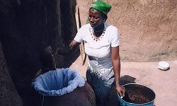 Damou Akou, a Ghanaian Red Cross Guinea worm volunteer, teaches others how to filter water collected from a near by Guinea worm-infested water source, by using a filter cloth.
