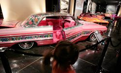 """Visitors to the Peterson Automobile Museum examine a 1964 Chevrolet Impala """"Gypsy Rose"""" lowrider in Los Angeles, Calif."""