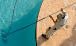 You can skim the pool for leaves yourself, but hire a professional to service the heater.