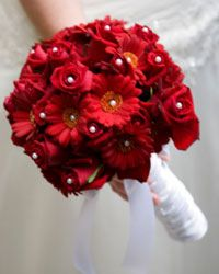 Delicate pearl-tipped pins add subtle luxury to this red bouquet.