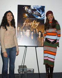 """Series actresses Morena Baccarin and Gina Torres pose with a """"Firefly"""" poster at the 2003 Los Angeles Comic Book and Science Fiction Convention."""