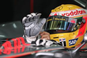 British McLaren-Mercedes driver Lewis Hamilton puts his gloves on in the pits of the Sakhir racetrack, in Manama, during the second practice session of the Bahrain Formula One grand Prix.