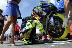 Valentino Rossi of Italy kneels next to his motorbike prior to the start of the German motorcycling Grand Prix at the Sachsenring in Hohenstein-Ernstthal.
