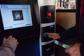 A user learns how to scan his palm to ensure that he cannot exchange more than $1,000 in a single day on the world's first bitcoin ATM at Waves Coffee House in Vancouver, B.C., in 2013.