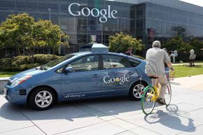 A bicyclist rides by a Google self-driving car at the Google headquarters in Mountain View, Calif. in 2012.