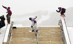 Three snowboarders compete in the Yahoo! Sports Big Air and Style Jib Jam at the Park City Mountain Resort in 2002.