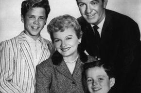 """Image Gallery: Parenting June Cleaver (played by Barbara Billingsley), surrounded by her adoring family, in this 1957 still from """"Leave it to Beaver."""" With her always-clean house and her unflappable demeanor, she's one TV mom we'd like to be. See pictures of parenting."""