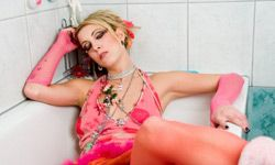 This young woman in glamour punk style lies in the empty bathtub and holds her head. Could it be a hangover?