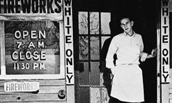 "A young man stands in the doorway of a store marked ""White Only, "" circa 1950., in the U.S. South."