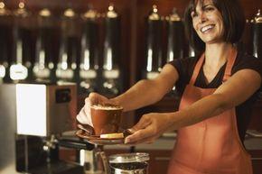 A barista presenting cappuccino to a customer.