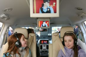 Willa Norris, 8, left, and Hannah Fowler, 10, sit in a 2008 Chrysler Town and Country minivan during a demonstration of Sirius Backseat TV.