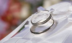 The wedding rings symbolize the binding of the bride to the groom -- although not literally, as the tradition once went.