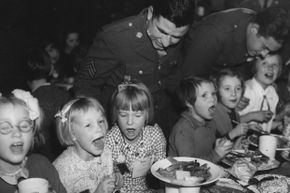 Soldiers serve children Thanksgiving dinner during World War II, around the time the U.S. Congress declared Thanksgiving an official holiday.