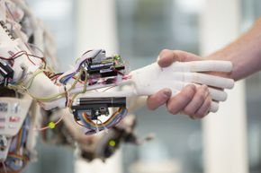 ROBOY, a humanoid robot developed by the University of Zurich's Artificial Intelligence Lab, shakes hands with his human counterpart on June 21, 2013. By using 3D-printing technology, ROBOY was developed within only nine months.