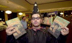 """A Barnes and Noble employee in Atlanta holds copies of """"Harry Potter and the Goblet of Fire."""""""