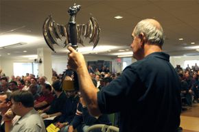 Joe McIntyre holds up a hatchet as the contents of Curt Schilling's bankrupt video game company 38 Studios are auctioned off in 2010.