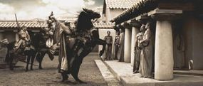 The Messenger (Peter Mensah), brandishing the skulls of kings who dared to stand against the might of the Persian empire, arrives in Sparta to deliver Xerxes' message.