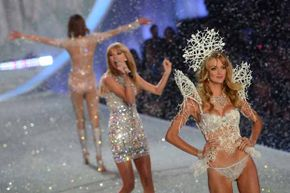Model Lindsay Ellingson struts the runway in her 3-D-printed headpiece as Taylor Swift (center) sings during the 2013 Victoria's Secret Fashion Show.