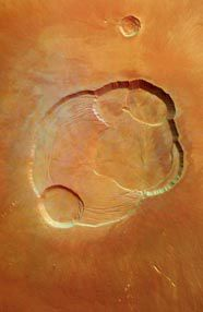 """The top of Olympus Mons is pictured above. This is the largest mountain in our solar system. It is an extinct volcano that is more than three times taller than Mount Everest. The depressions in this picture are called """"caldera pits."""""""
