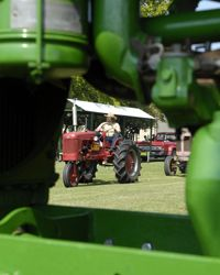 Framed by a John Deere tractor engine, Tom Jenkins drives his antique Farmall tractor during the 15th Arkansas Antique Tractor and Engine Show, in Scott, Ark.