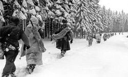Troops of the 82nd Airborne Division travel a snow-covered fire break in the woods as they move forward in the Ardennes region in Belgium, on Jan. 28, 1945.