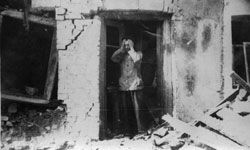 A Polish farmer stands in the doorway of his home, head in his hands in despair, and surveys the wreckage caused by a German air raid during the invasion of Poland.