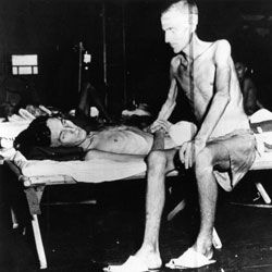 Two emaciated soldiers, liberated from the Japanese prison camp on Formosa, recover from their ordeal aboard the USS Block Island.
