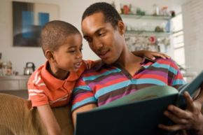 father reading a book to young son