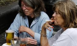 Two women chat as they drink and smoke in central London, on Aug. 6, 2008.