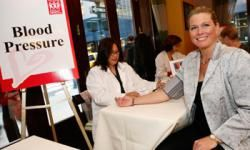 """Actress and model Emme Aronson, right, has her blood pressure checked at the """"Sister to Sister Everyone Has a Heart"""" breakfast for women business executives, in New York."""