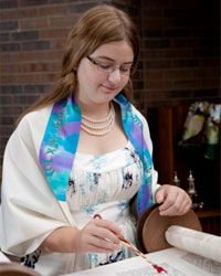 A girl reads from the Torah at her bat mitzvah.
