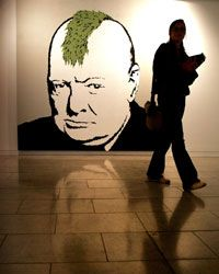 A woman walks past a picture of Winston Churchill by artist Banksy.
