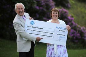 75 percent of lottery winners opt for lump sum payments. UK winners Brian and Joan Caswell pose with their big check in 2009.