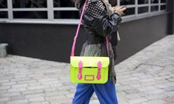 Ahead of the trends: A woman carries a Cambridge satchel in neon at London Fashion Week 2012.