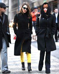 On the street in Soho: Jessica Alba, wearing bright yellow skinny jeans beneath a classic black coat.