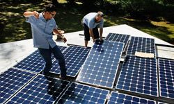 Workers install a solar panel system on the roof of a home in Gainesville, Fla.