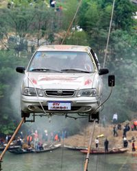 Liu Suozhu from China's Henan province drives a car on two steel ropes above the Miluo River in Pingjiang, central China's Hunan province, on April 27, 2008.