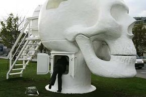 """A woman peeks inside Joep van Lieshout's """"Wellness Skull"""" at the Karlsplatz in Vienna, during its 2008 exhibition there."""