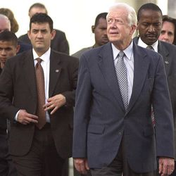 Jimmy Carter is shown here followed closely by security guards in 2002, decades after his term as U.S. president.