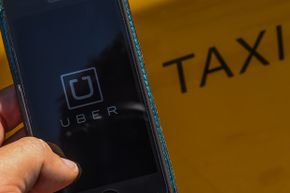 The smartphone app 'Uber' logo is displayed on a mobile phone next to a taxi in Barcelona, Spain.