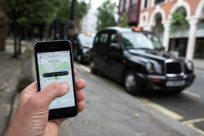 A smartphone displays the 'Uber' mobile application which allows users to hail private-hire cars from any location in London, England.