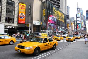 Yellow cabs travel South on Broadway in Times Square in New York, New York.