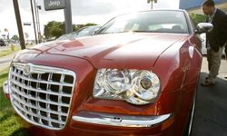 A customer looks at a new Chrysler 300 on a dealer lot in Dearborn, Mich.